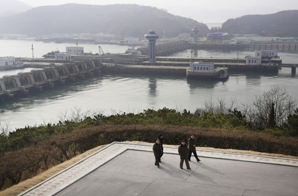 In this Feb. 2, 2019, photo, North Koreans men walk with the background of the West Sea Barrage in Nampo, North Korea. North Korea is exploring two am