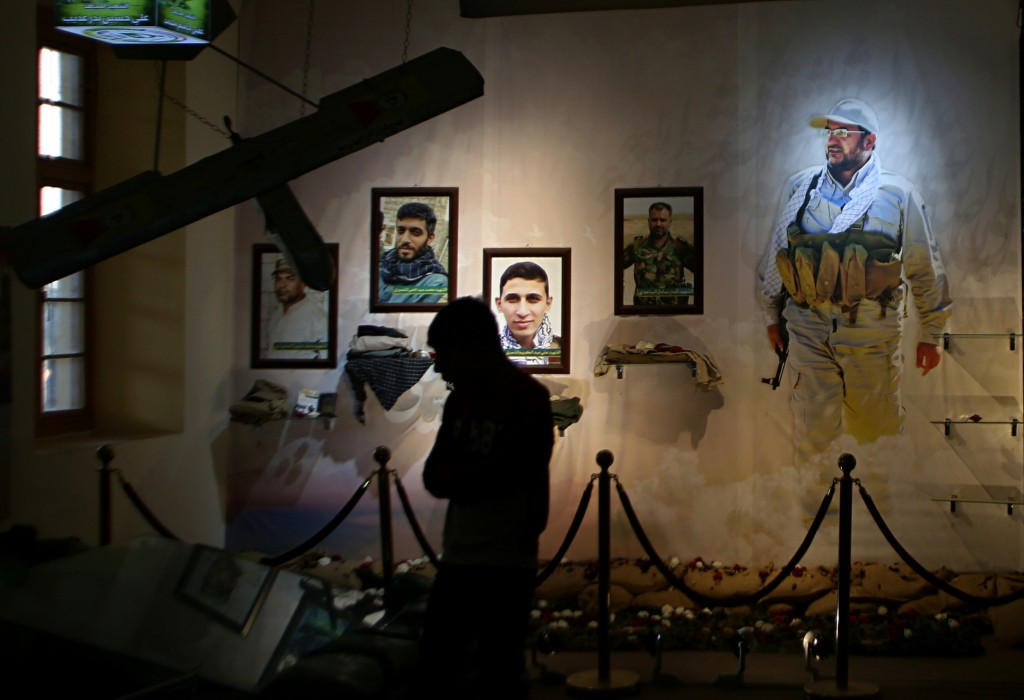 In this Friday, Feb. 1, 2019 photo, pictures of militiamen who died fighting the Islamic State group over the past four years and weapons are on displ...