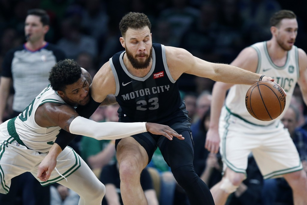Boston Celtics' Marcus Smart, left, defends against Detroit Pistons' Blake Griffin, right, during the first half of an NBA basketball game in Boston, ...