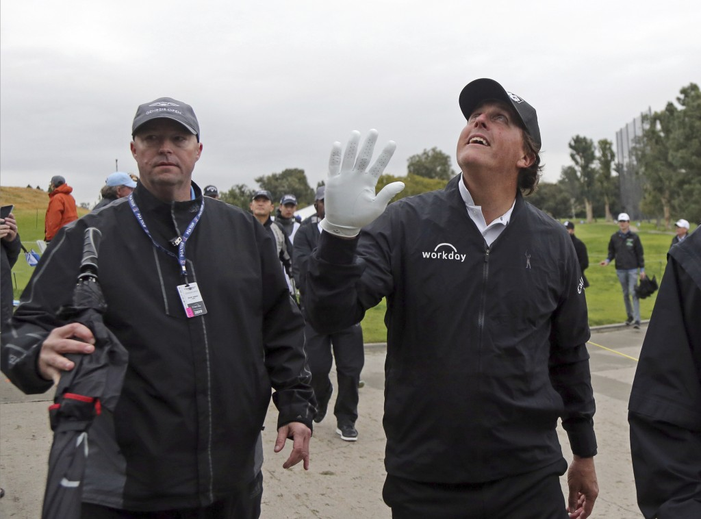 Phil Mickelson waves to someone who shouted a greeting from the grandstand during the pro-am round of the Genesis Open golf tournament at Riviera Coun...