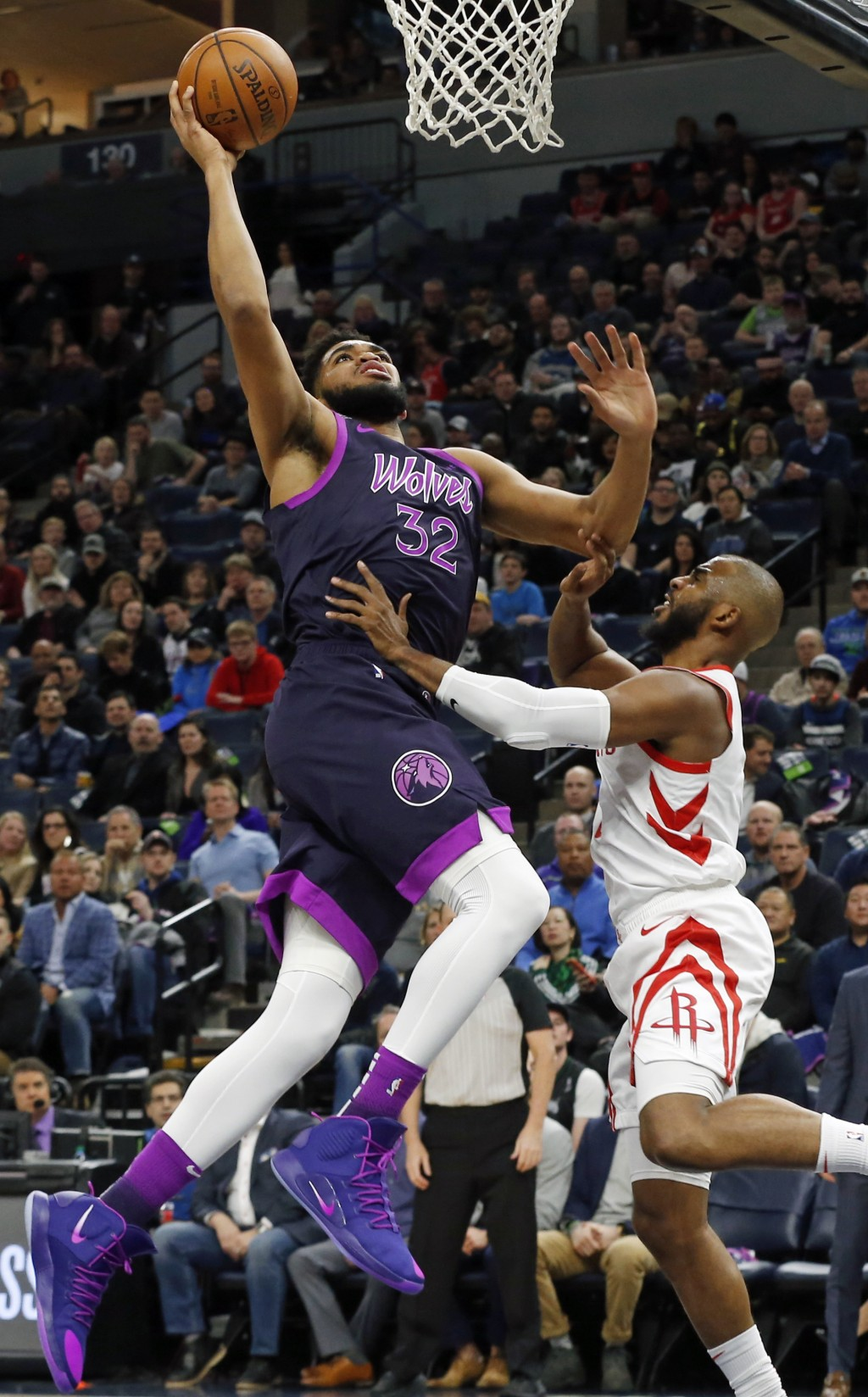 Minnesota Timberwolves' Karl-Anthony Towns, left, goes in for a layup as Houston Rockets' Chris Paul defends in the first half of an NBA basketball ga