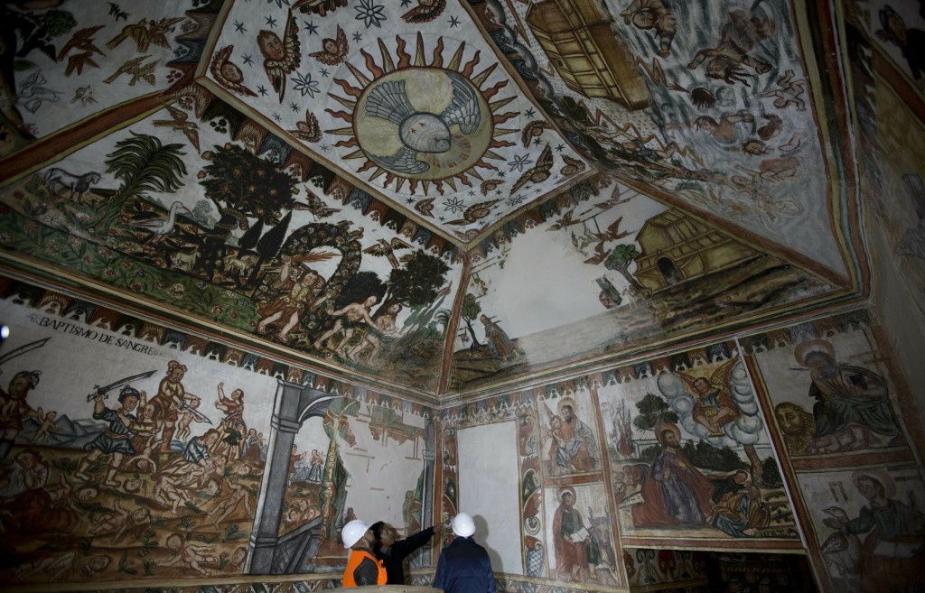 In this Feb. 9, 2019 photo, Father Rafael Choque, center, and architects, experts in restoration, look at the murals of the local church of Curahuara ...