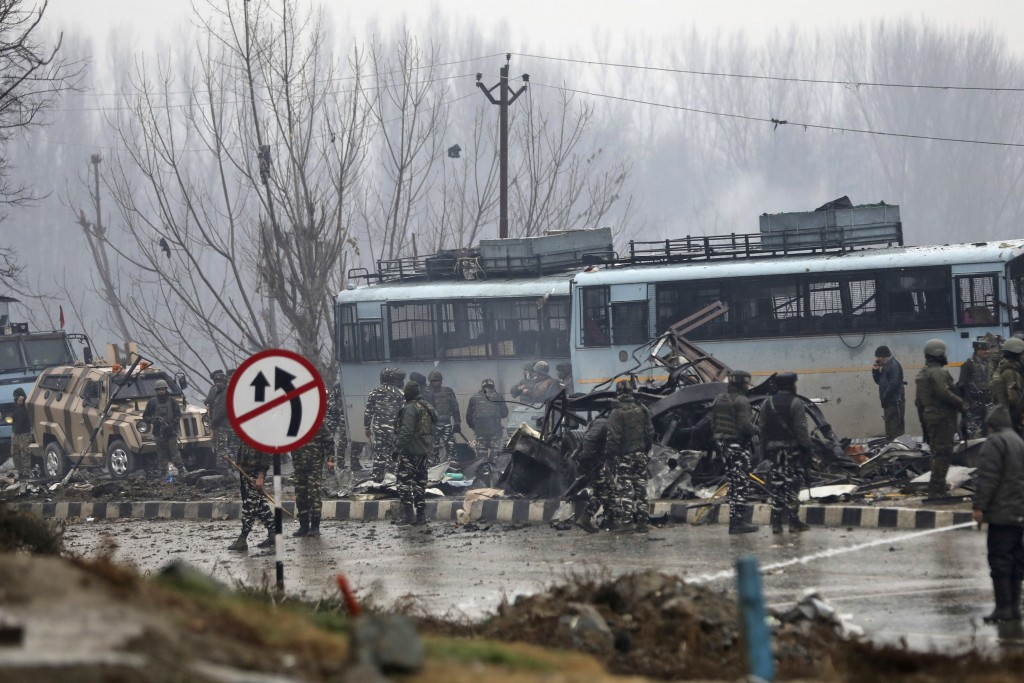 Indian paramilitary soldiers stand by the wreckage of a bus after an explosion in Pampore, Indian-controlled Kashmir, Thursday, Feb. 14, 2019. Securit...
