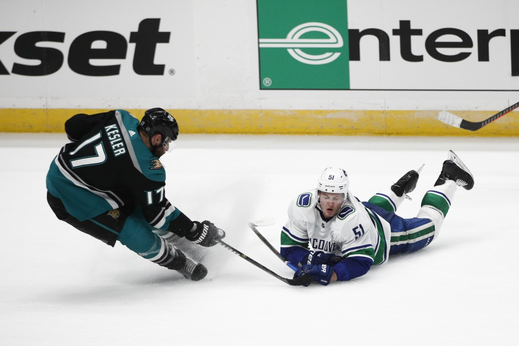 Vancouver Canucks' Troy Stecher, right, falls to the ice while competing for the puck with Anaheim Ducks' Ryan Kesler during the third period of an NH...