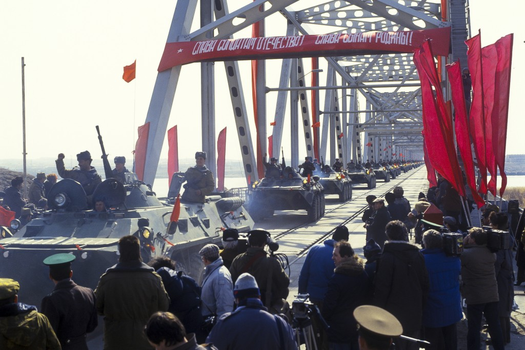 In this photo taken on Feb. 15, 1989, Soviet Army soldiers wave their hands as their unit crosses a bridge on the border between Afghanistan and then
