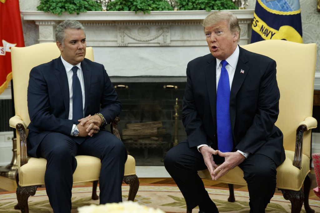 Colombian President Ivan Duque listens as President Donald Trump speaks during a meeting in the Oval Office of the White House, Wednesday, Feb. 13, 20...