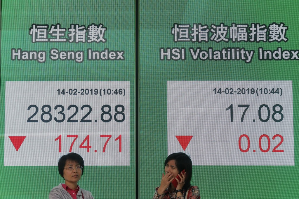 Two women stand in front of an electronic board showing Hong Kong share index outside a bank in Hong Kong, Thursday, Feb. 14, 2019. Asian stocks were ...