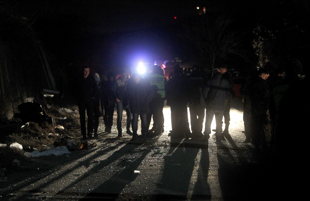 Police officers and investigators are silhouetted at the crash site at village of Laskarci, west of Skopje, North Macedonia, Wednesday, Feb. 13, 2019....