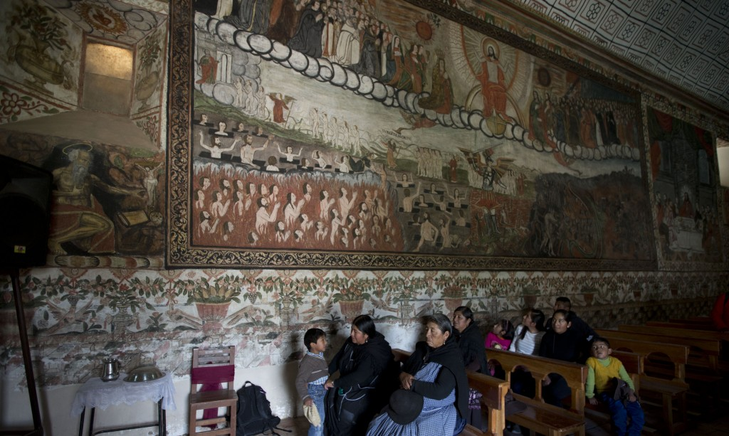 In this Feb. 9, 2019 photo, women attend Mass at the local church in Curahuara de Carangas, Bolivia. The church's location in on a high desert plateau