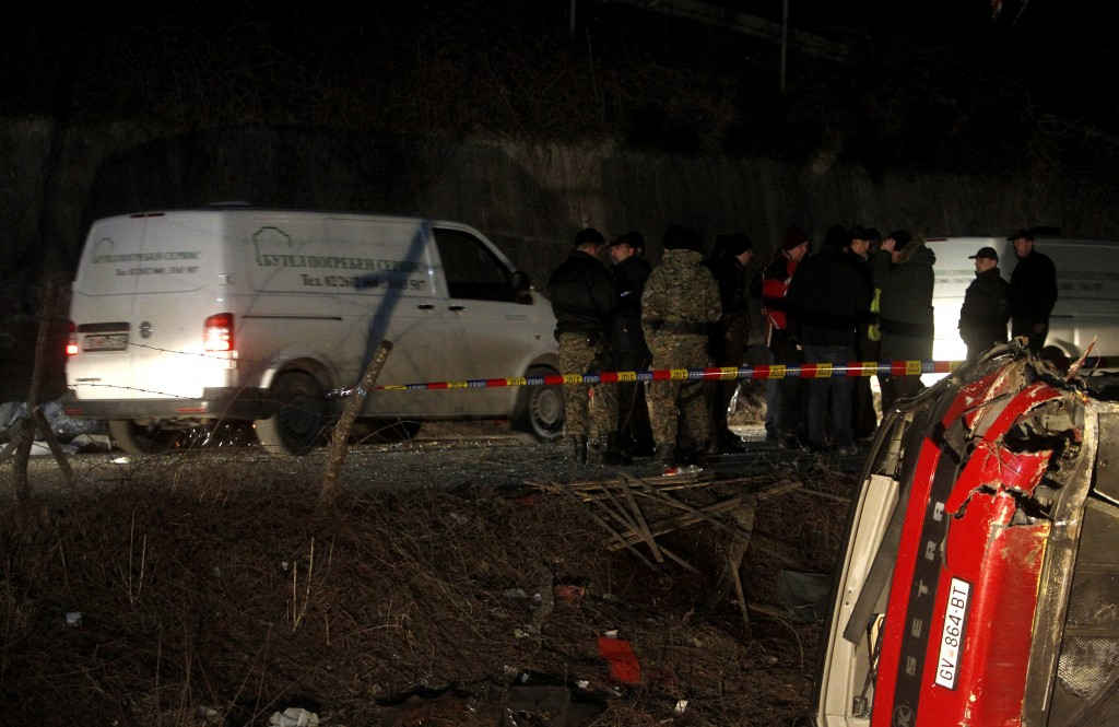 Police and investigators stand near the bus wreckage at the crash site at the village of Laskarci, west of Skopje, North Macedonia, Wednesday, Feb. 13...