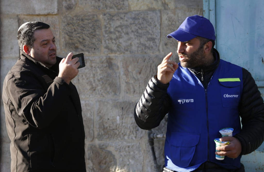 In this Tuesday, Feb. 12, 2019 photo, an Israeli settler, left, takes a picture of a Palestinian observer as he watches over children walking to schoo...