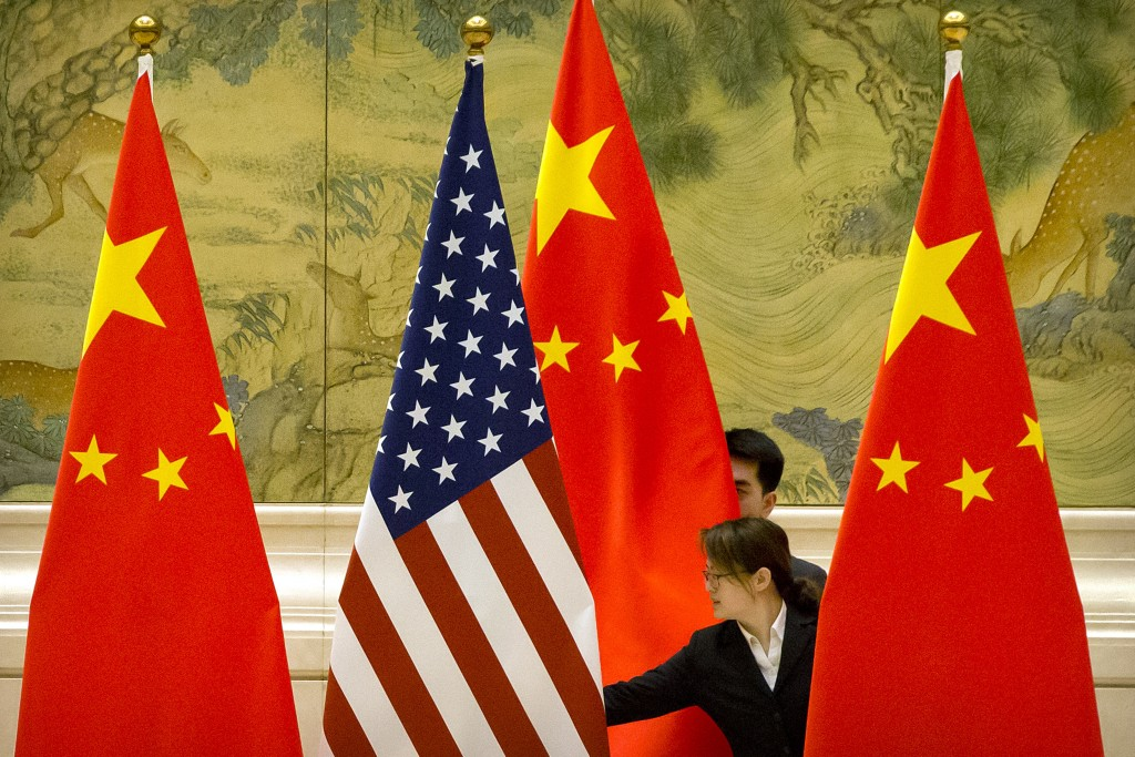 Chinese staffers adjust U.S. and Chinese flags before the opening session of trade negotiations between U.S. and Chinese trade representatives at the