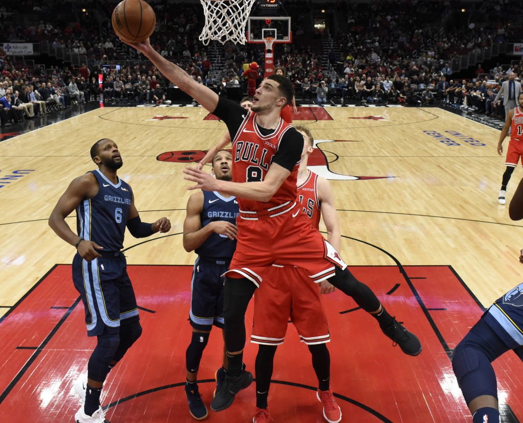 Chicago Bulls guard Zach LaVine (8) drives to the basket as Memphis Grizzlies forward CJ Miles (6) stands nearby during the first half of an NBA baske...