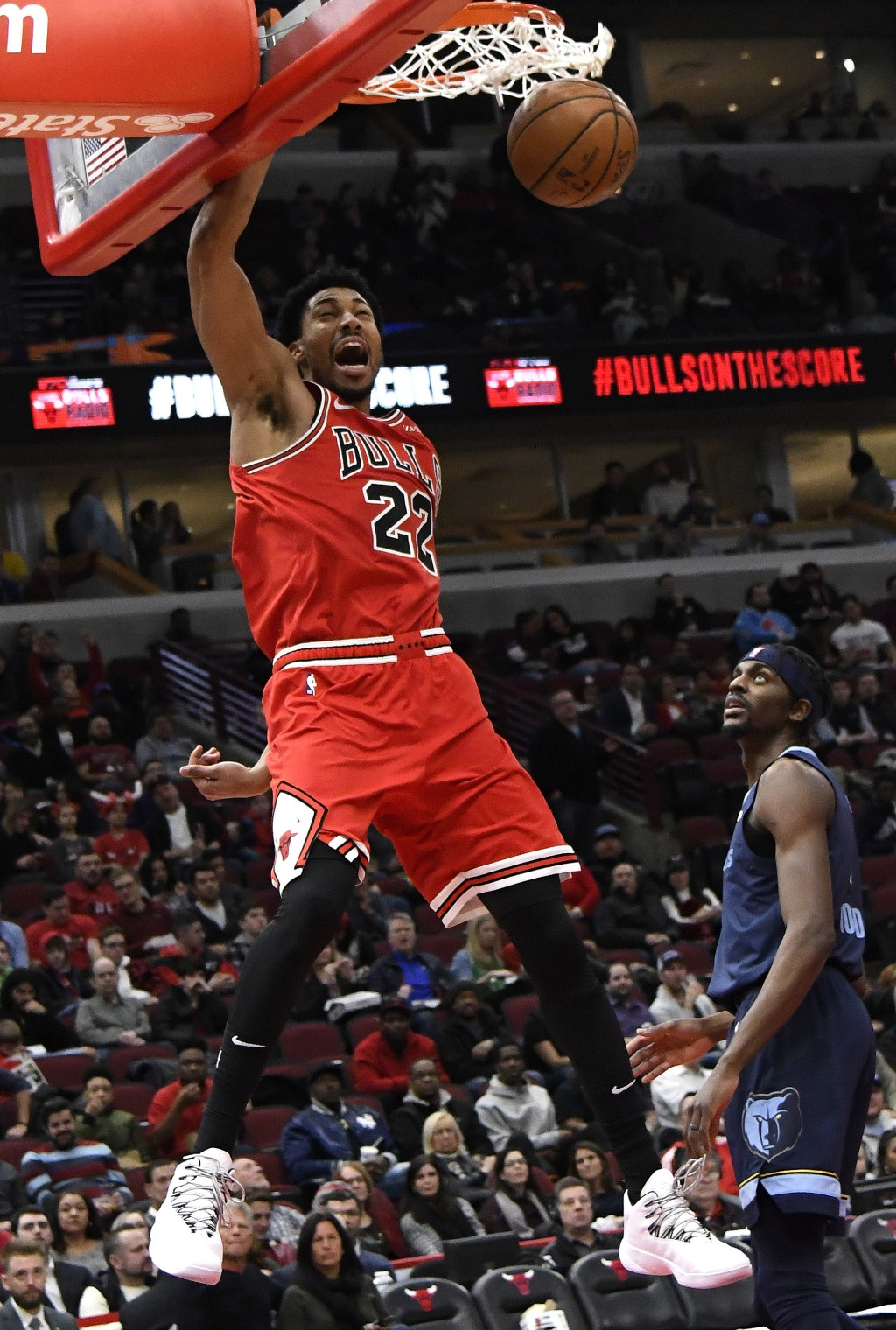 Chicago Bulls forward Otto Porter Jr. (22) dunks the ball as Memphis Grizzlies forward Justin Holiday (7) stands nearby during the second half of an N...