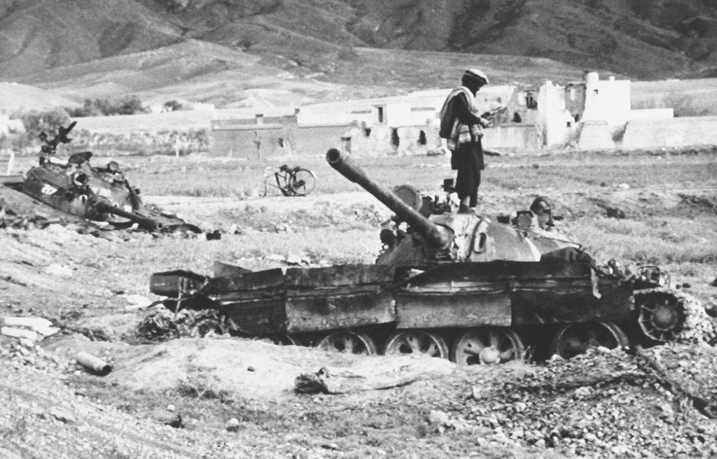 FILE - In this file photo taken April 2, 1989, an Afghan guerrilla stands on top of one of the Soviet-made army tanks captured near Jalalabad, in Afgh