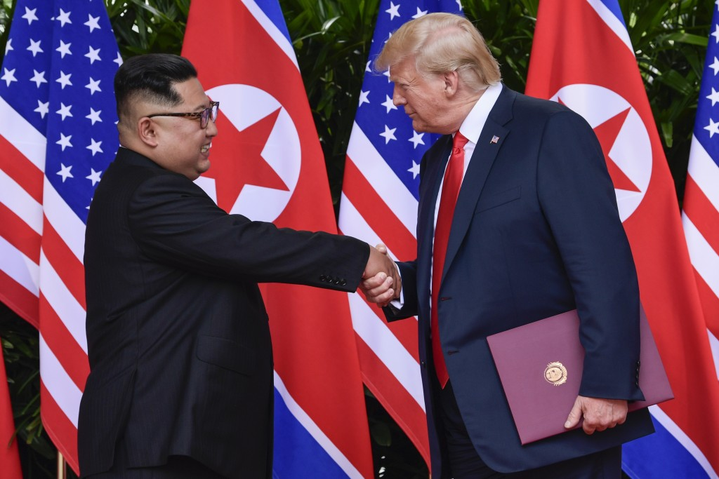 FILE - In this June 12, 2018 file photo, North Korea leader Kim Jong Un and U.S. President Donald Trump shake hands at the conclusion of their meeting...