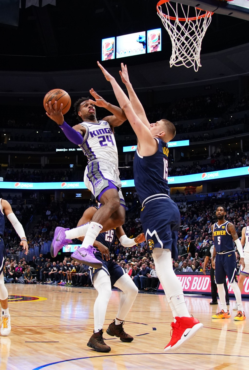 Sacramento Kings guard Buddy Hield (24) goes up for a shot against Denver Nuggets center Nikola Jokic (15) during the first half of an NBA basketball