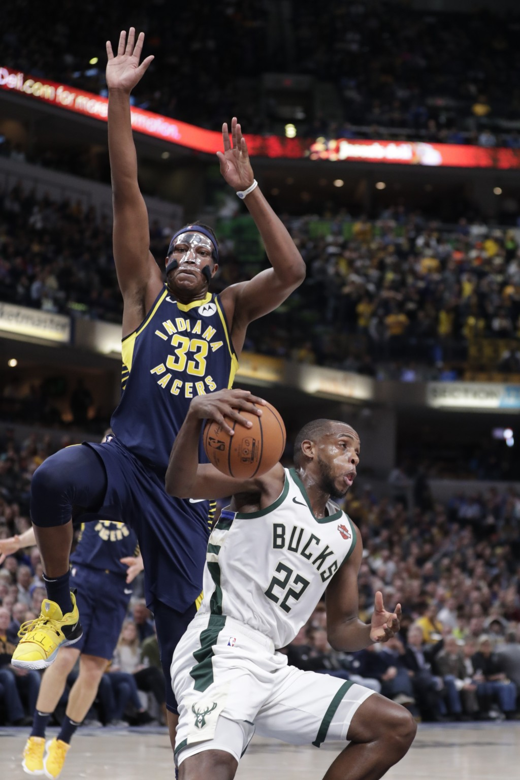 Milwaukee Bucks forward Khris Middleton (22) fakes under Indiana Pacers center Myles Turner (33) during the second half of an NBA basketball game in I...