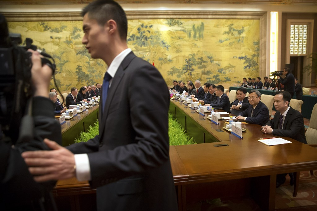 A security official escorts journalists from the opening session of trade negotiations between U.S. and Chinese trade representatives at the Diaoyutai...
