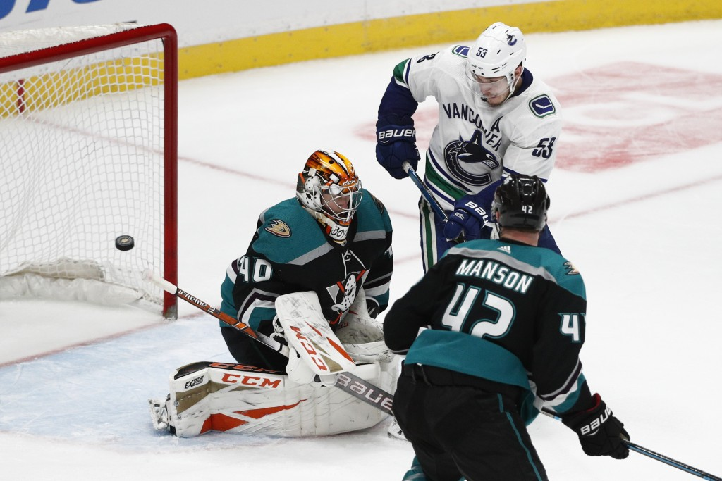 Anaheim Ducks goaltender Kevin Boyle, left, deflects the puck as teammate Josh Manson and Vancouver Canucks' Bo Horvat watch during the third period o