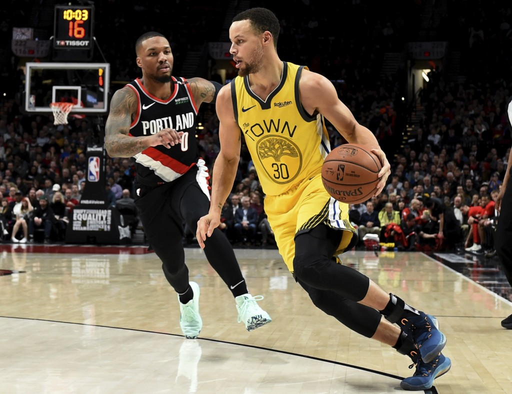 Golden State Warriors guard Stephen Curry, right, drives to the basket past Portland Trail Blazers guard Damian Lillard during the first half of an NB...