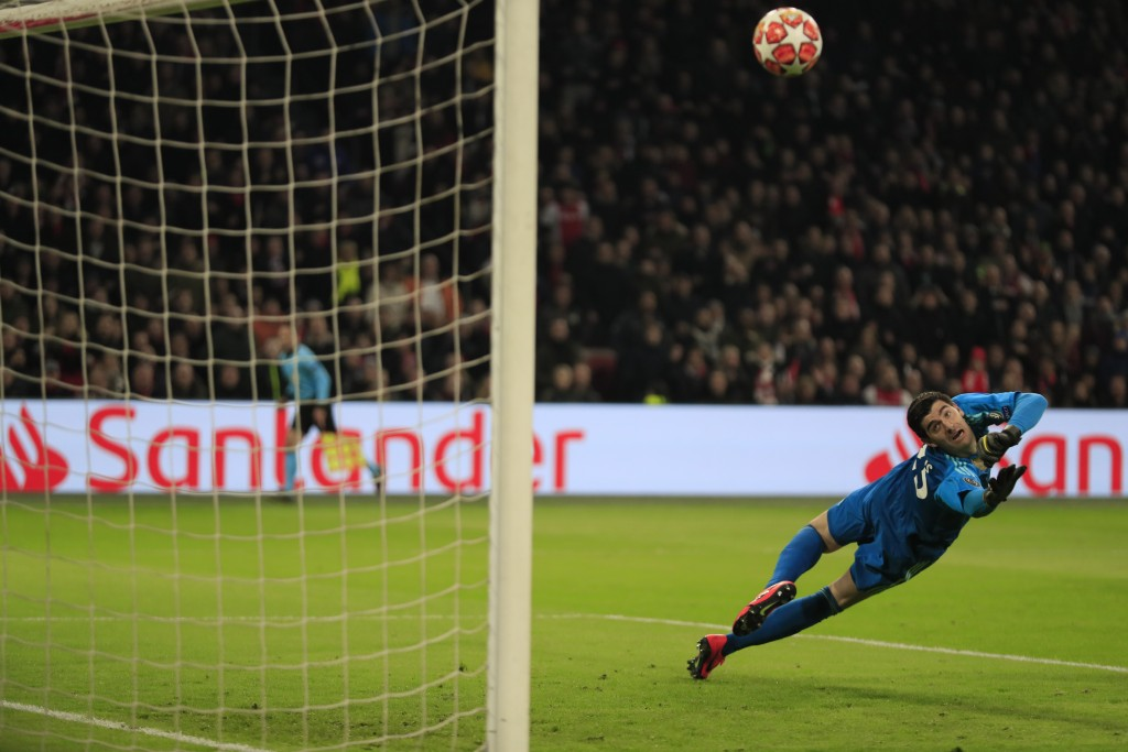 Real goalkeeper Thibaut Courtois dives for a ball fired off the post by Ajax's Dusan Tadic during the first leg, round of sixteen, Champions League so...