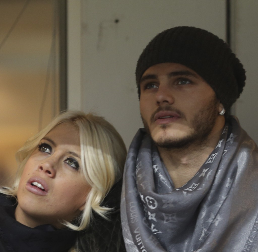 FILE - In this Jan. 13, 2014 file photo, Inter Milan forward Mauro Icardi, of Argentina, is flanked by his wife Wanda Nara as they sit in the stands p...