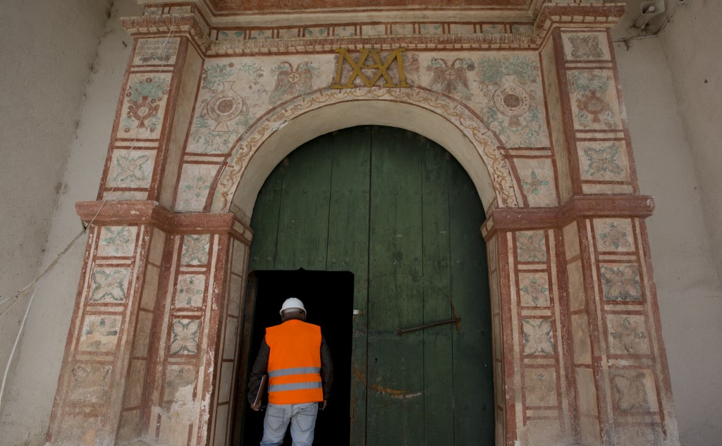 In this Feb. 9, 2019 photo, an architect, an expert in restoration, enters the local church in Curahuara de Carangas, Bolivia. Abandonment and heavy r