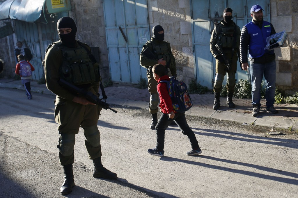 In this Tuesday, Feb. 12, 2019 photo, A Palestinian observers, right, watches as children walk past Israeli soldiers on their way to school in the Wes...