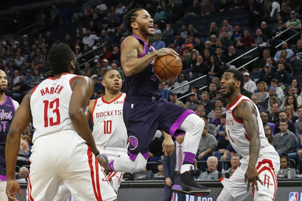 Minnesota Timberwolves' Derrick Rose, center, goes airborne for a layup as Houston Rockets' James Harden, left, Eric Gordon and Michael Carter-William