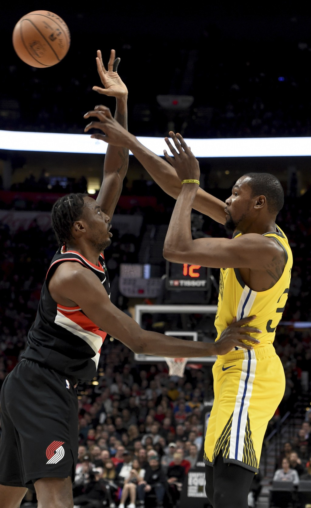 Golden State Warriors forward Kevin Durant, right, passes the ball over Portland Trail Blazers forward Al-Farouq Aminu during the first half of an NBA...
