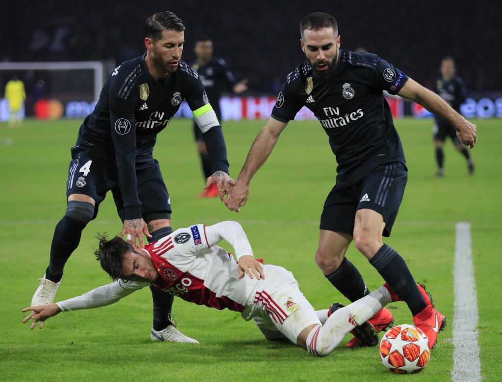 Ajax's Nicolas Tagliafico, center, is tackled by Real defender Dani Carvajal, right, and Real defender Sergio Ramos during the first leg, round of six...