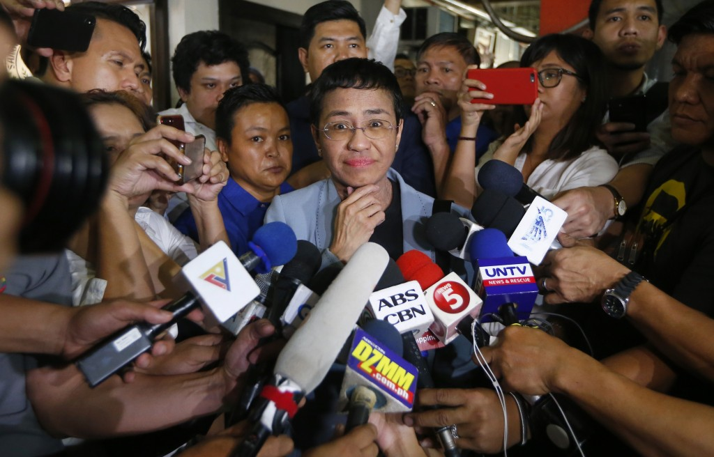 Maria Ressa, center, the award-winning head of a Philippine online news site Rappler, listens to a reporter's question after posting bail at a Regiona...