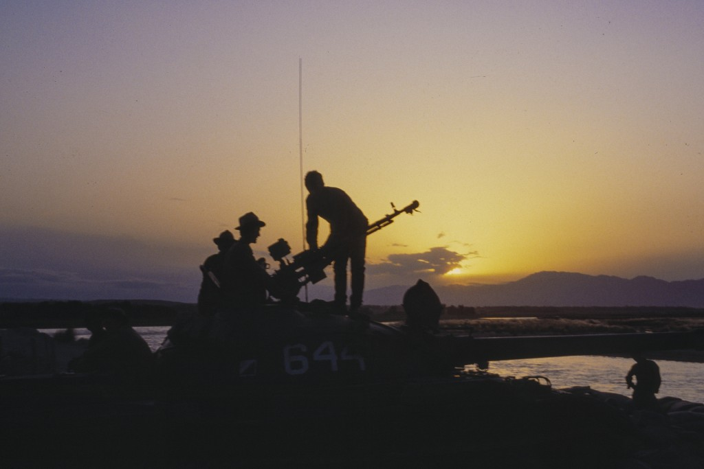 In this photo taken photo taken in September 1984, Soviet Army soldiers stand atop of a tank at a outpost during sunset in Afghanistan. When the Sovie