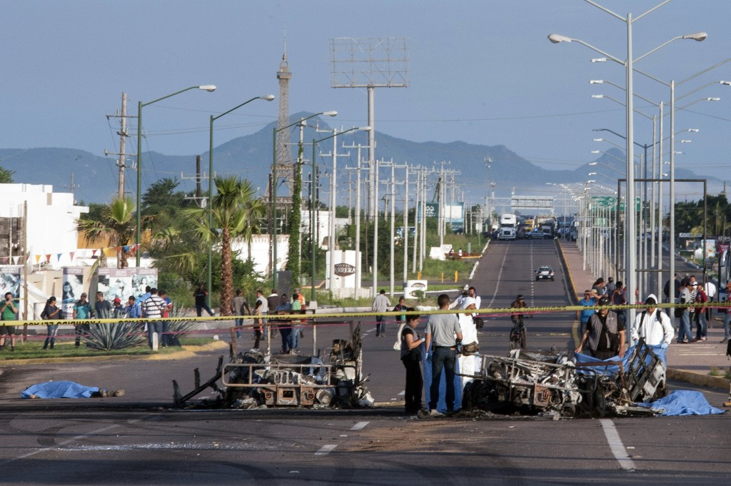 FILE - In this Sept. 30, 2016 file photo, police investigators examine the site where a military convoy was ambushed with grenades and high-powered gu...