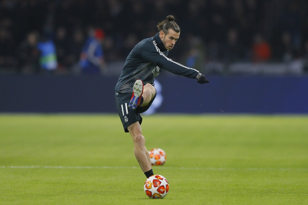 Real midfielder Gareth Bale shoots the ball as warming up during the first leg, round of sixteen, Champions League soccer match between Ajax and Real ...