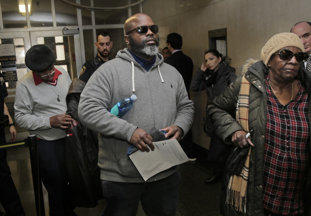Friends and family of Timothy Caughman, including his cousin Richard Peek, center, leave the courtroom after the sentencing of James Jackson in New Yo...