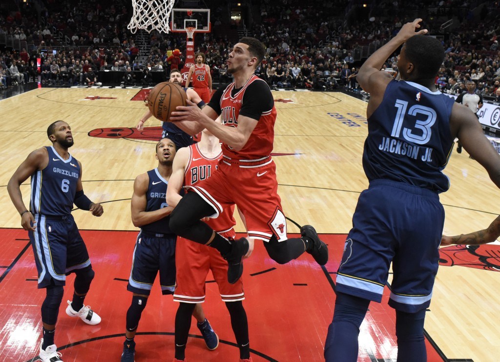 Chicago Bulls guard Zach LaVine, center, drives to the basket as Memphis Grizzlies forward Jaren Jackson Jr. (13) defends him during the first half of