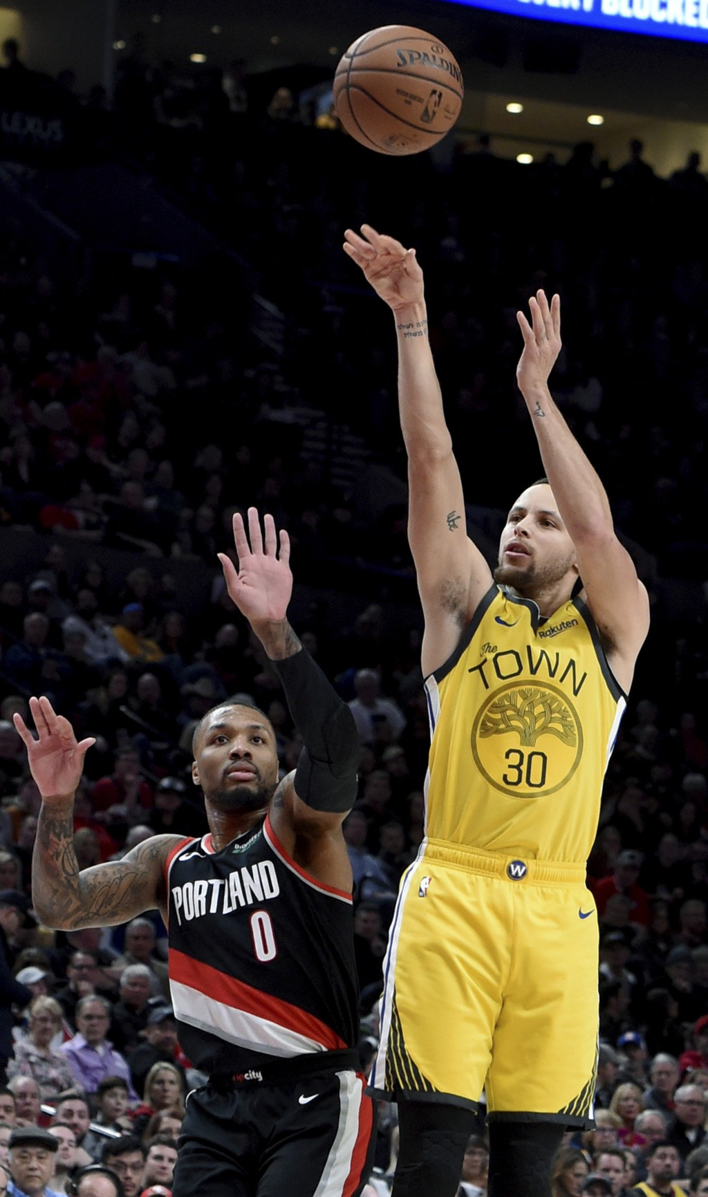 Golden State Warriors guard Stephen Curry, right, hits a shot next to Portland Trail Blazers guard Damian Lillard during the first half of an NBA bask