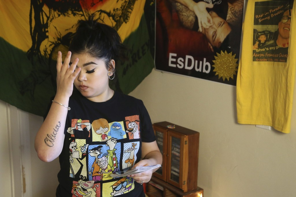 Seanna Leilani Chavez, the sister of Aaron Francisco Chavez, pauses as she looks at family photos as she stands next to a shrine for Aaron, including ...