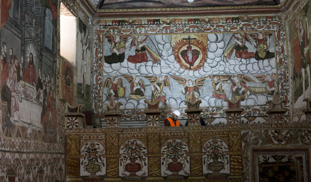 In this Feb. 9, 2019 photo, an architect, expert in restoration, inspects the murals of the local church in Curahuara de Carangas, Bolivia. On the out...