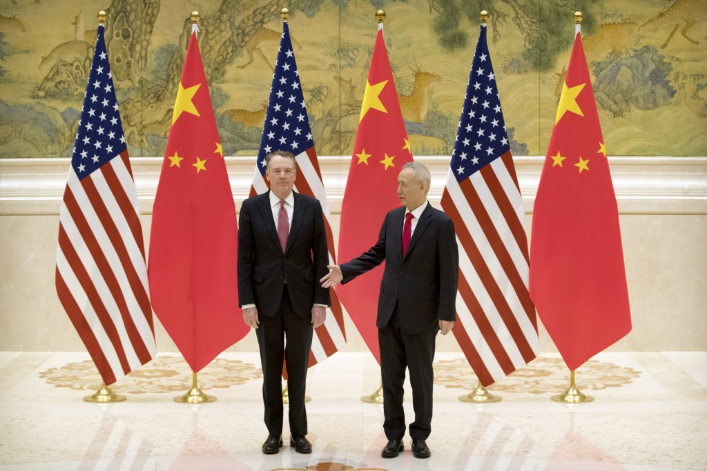 Chinese Vice Premier and lead trade negotiator Liu He, right, reaches to shake hands with U.S. Trade Representative Robert Lighthizer before the openi...