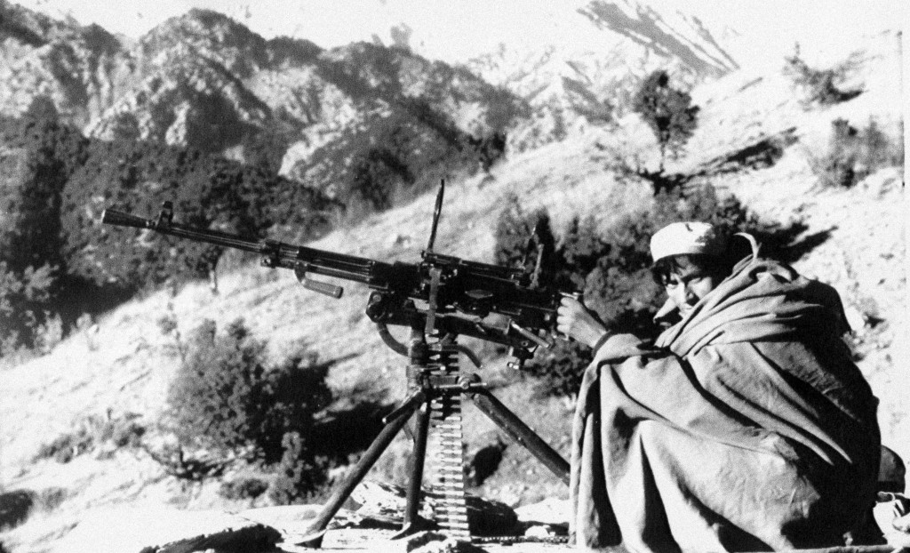 FILE - In this file photo taken on Jan. 1, 1988, an Afghan rebel armed an anti-aircraft machine gun gets ready to fire at position in the Nangarhar pr...