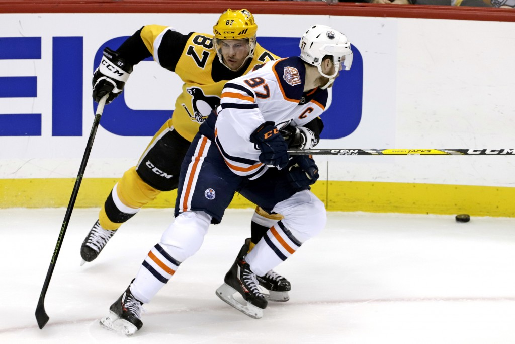 Pittsburgh Penguins' Sidney Crosby (87) defends against Edmonton Oilers' Connor McDavid (97) during the first period of an NHL hockey game in Pittsbur