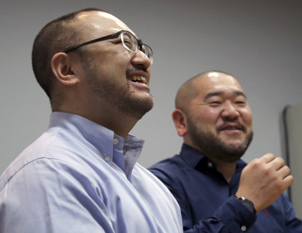 In this Jan. 28, 2019, photo, Kenji Aiba, left, and his partner Ken Kozumi laugh during an interview with The Associated Press in Tokyo. Kozumi and Ai