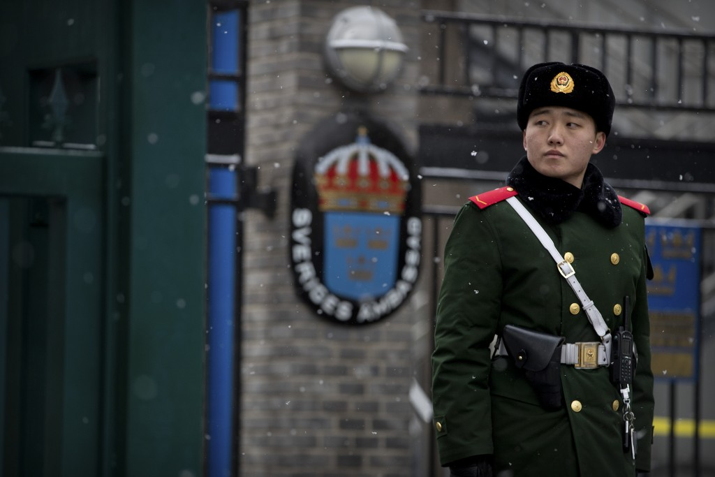 A paramilitary police officer stands guard at the gate of the Swedish Embassy in Beijing, Thursday, Feb. 14, 2019. The embassy said Thursday that Amba...