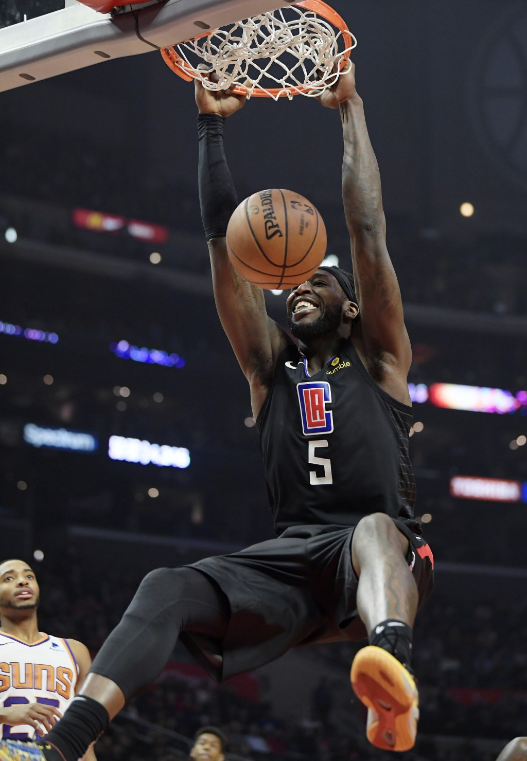 Los Angeles Clippers forward Montrezl Harrell dunks as Phoenix Suns forward Mikal Bridges watches during the first half of an NBA basketball game Wedn