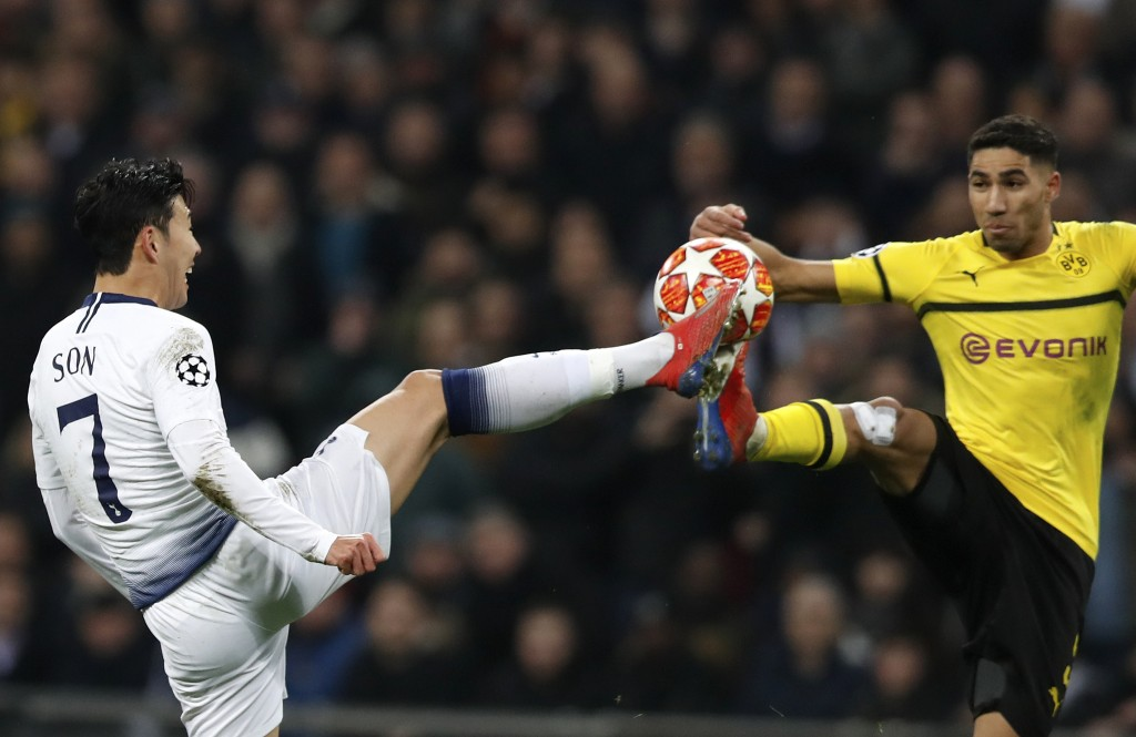 Tottenham midfielder Son Heung-min fights for the ball with Dortmund defender Achraf Hakimi, right, during the Champions League round of 16, first leg