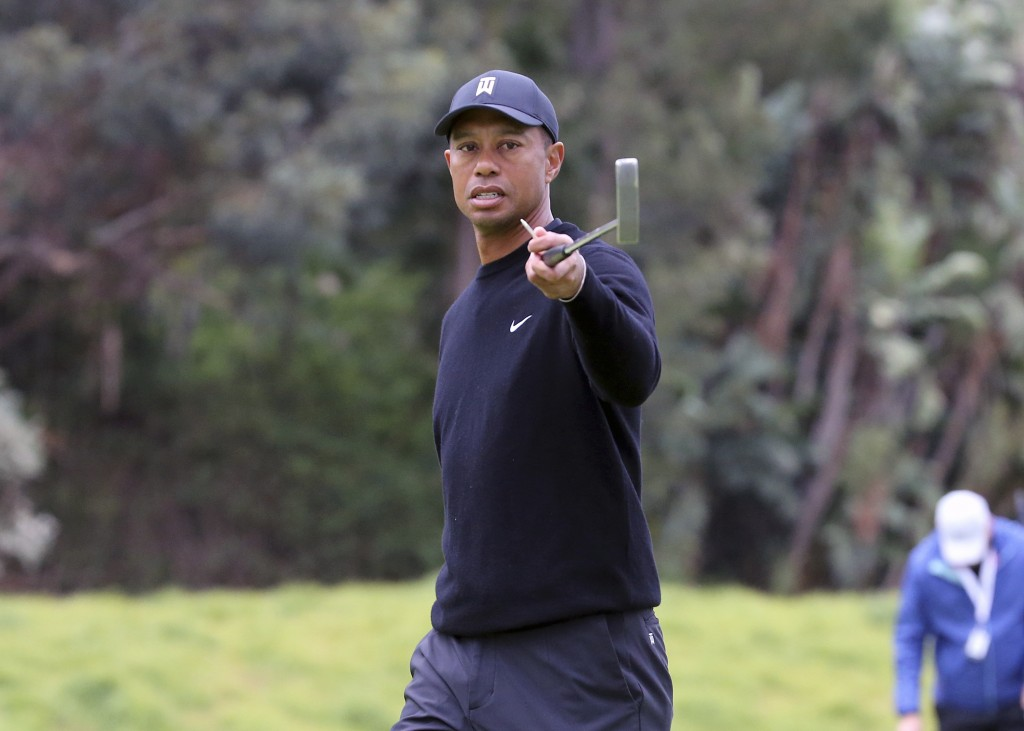 Tiger Woods warns spectators that someone is hitting behind them during the Pro-Am round of the Genesis Open golf tournament at Riviera Country Club i...