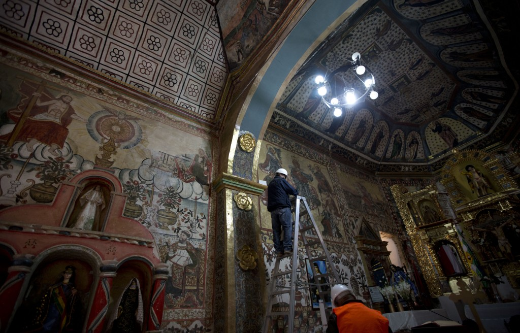 In this Feb. 9, 2019 photo, architects, experts in restoration inspect the murals of the local church in Curahuara de Carangas, Bolivia. Heavy rains r
